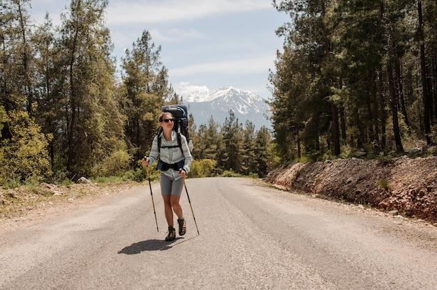 Vrouwelijke reiziger die op een bosweg loopt