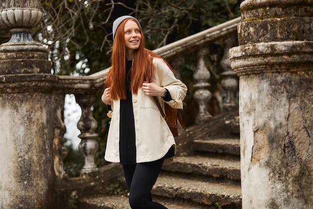 Vrouwelijke reiziger gaat de trap af van een oud gebouw en kijkt weg in contemplatie en geniet van aan...
