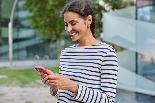 Vrouwelijke reiziger gebruikt app en gps-zoekt naar richtingsteksten tijdens het wandelen in de stad draagt vrijetijdskleding berichten met vriend poseert alleen buiten leest positieve feedback onder post