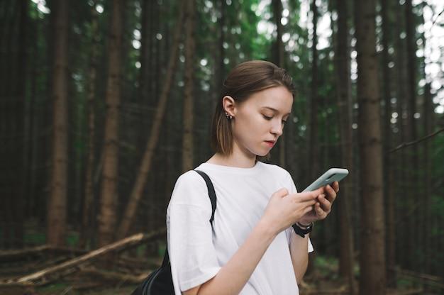 Vrouwelijke reiziger gebruikt haar app voor smartphonekaarten om de weg te vinden vanuit het bergbos