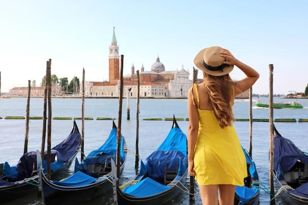Vrouwelijke reiziger geniet van een prachtig uitzicht op het venetiaanse kanaal met gondels die drijven in venetië, italië