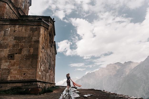 Vrouwelijke reiziger in de buurt van gergeti trinity church or tsminda sameba. stepantsminda, georgia. mount kazbegi.