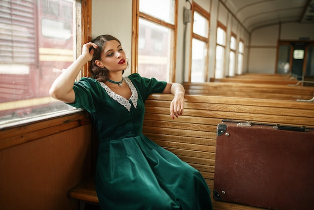 Vrouwelijke reiziger in retro trein, oud wagenbinnenland. spoorwegreis. vintage reis