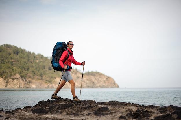 Vrouwelijke reiziger in zonnebril loopt in de buurt van de zee