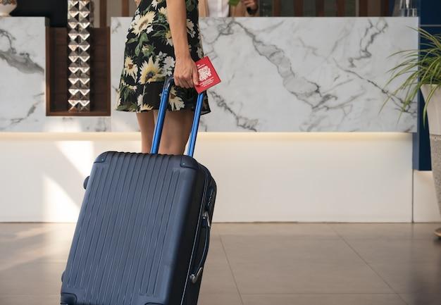Vrouwelijke reiziger met bagage die naar de incheckbalie van het hotel loopt