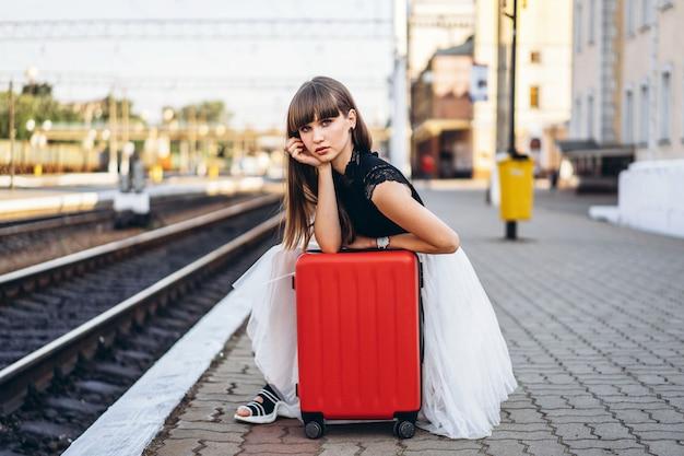 Vrouwelijke reiziger met de rode trein van het kofferwachten op station