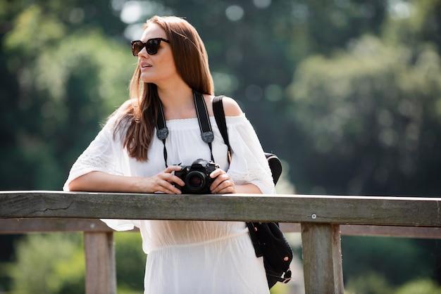 Vrouwelijke reiziger met een professionele camera voor nieuwe herinneringen