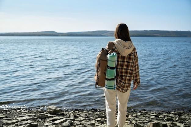 Vrouwelijke reiziger met rugzak die zich dichtbij rivier dniester bevindt