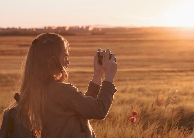 Vrouwelijke reiziger met rugzak maakt een foto met oude retro reel camera
