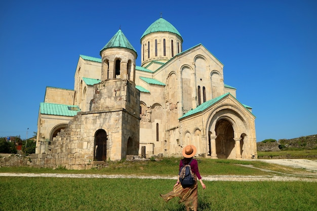Vrouwelijke reiziger onder de indruk van de bagrati-kathedraal in koetaisi, georgië
