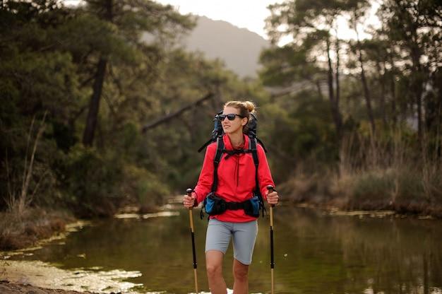 Vrouwelijke reiziger staat door bos rivier kust