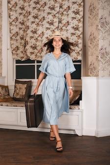 Vrouwelijke reiziger staat in de kamer met bagage.