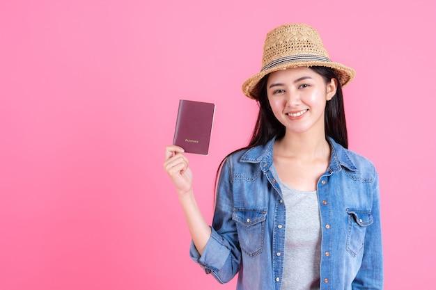 Vrouwelijke reiziger traw hoed draagt houdt paspoort portret van vrij lachende gelukkige tiener op roze