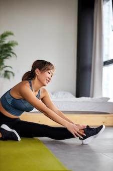 Vrouwelijke rekoefening op vloer thuis, kopieer ruimte. yoga, pilates, sporten