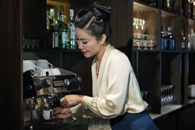 Vrouwelijke restaurantmanager die een kopje koffie maakt om 's avonds meer energie op te doen voor de rest