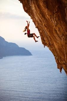 Vrouwelijke rock klimmer die van een klif valt tijdens het klimmen