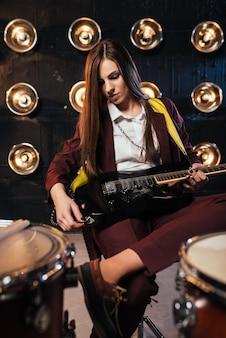 Vrouwelijke rockgitarist in pak zit achter het drumstel