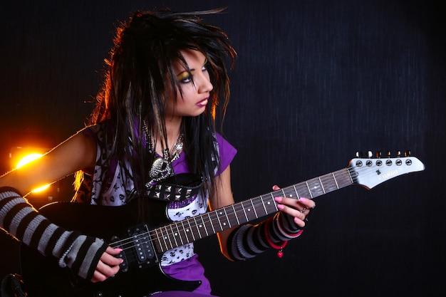 Vrouwelijke rockstar die op de rotsgitaar presteert