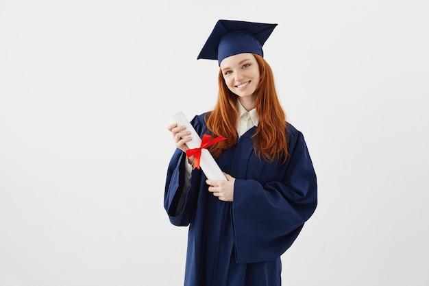 Vrouwelijke roodharige afgestudeerde student met diploma glimlachen. copyspace.