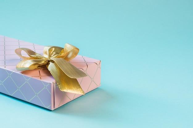 Vrouwelijke roze geschenkdoos met gouden lint op pittig pastelblauw. verjaardag. copyspace.