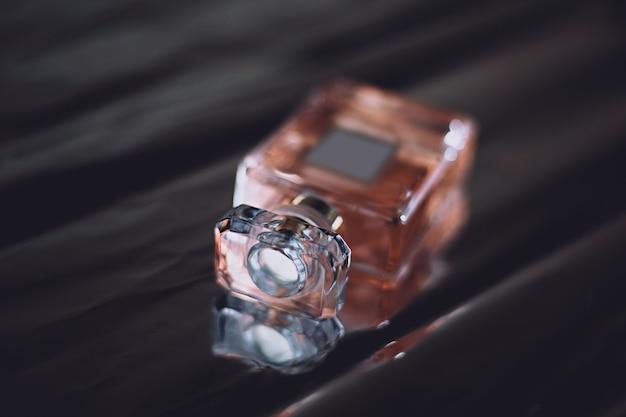 Vrouwelijke roze parfum op een donkere achtergrond