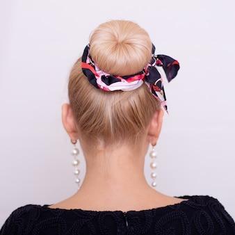 Vrouwelijke rug met blonde haarstijl en mode-band