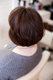 Vrouwelijke rug met kort, recht, donkerbruin haar in de kapsalon