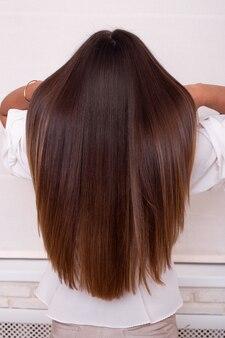 Vrouwelijke rug met lang recht donkerbruin haar in een kapsalon