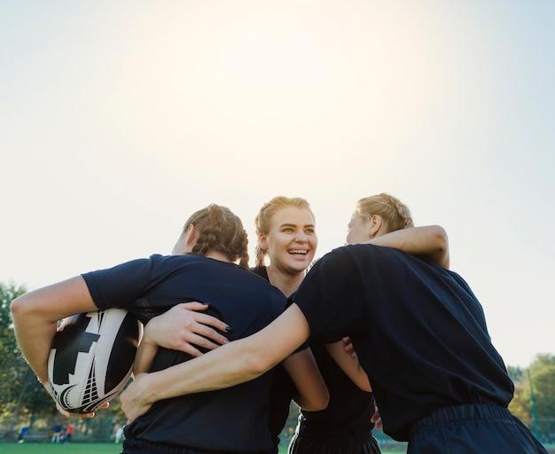 Vrouwelijke rugbyspelers die elkaar omarmen