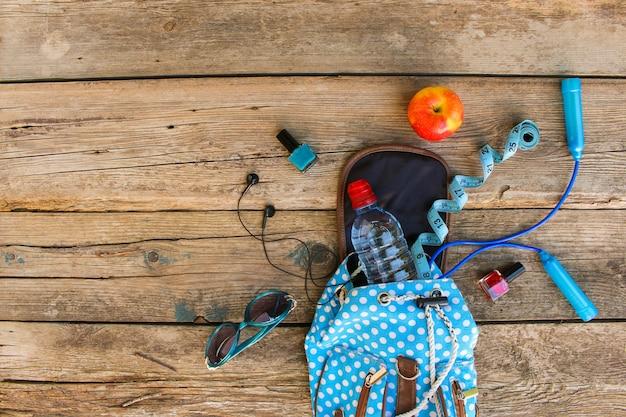 Vrouwelijke rugzak met sportartikelen, cosmetica, meetlint en water