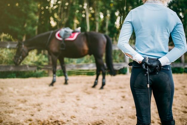 Vrouwelijke ruiter traint haar paard, paardrijden. paardensport, jonge vrouw en mooie hengst