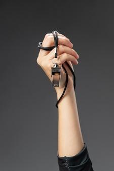 Vrouwelijke scheidsrechter hand met fluitje close-up