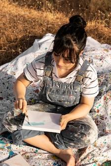 Vrouwelijke schilder buitenshuis met canvas en penseel