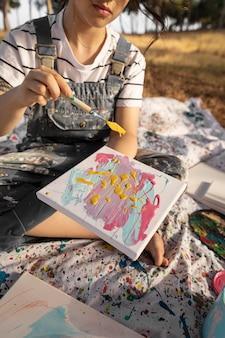 Vrouwelijke schilder buitenshuis met canvas