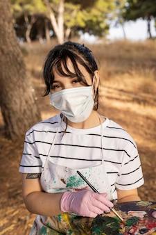 Vrouwelijke schilder buitenshuis met medisch masker