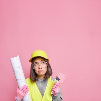Vrouwelijke schilder die betrokken is bij de renovatie en decoratie van het huis, gefocust boven, houdt een kwast vast en een blauwdruk draagt uniforme poses