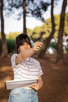 Vrouwelijke schilder die buitenshuis het landschap controleert
