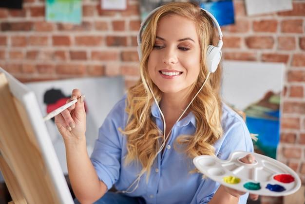 Vrouwelijke schilder die met hoofdtelefoons werkt