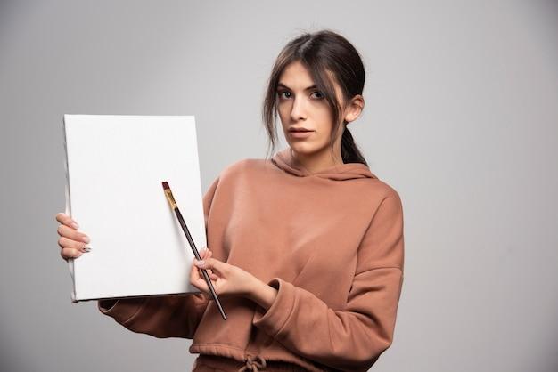 Vrouwelijke schilder poseren met verfborstel en canvas