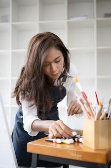 Vrouwelijke schilder schilderij foto met waterverf bij kunststudio.
