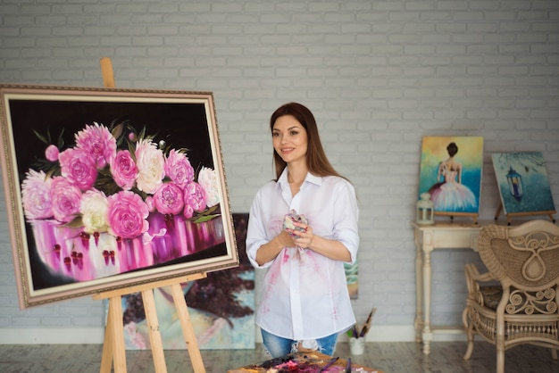 Vrouwelijke schilderstekening in kunststudio die schildersezel gebruiken. portret van een jonge vrouw die met olieverven schildert, zijaanzichtportret