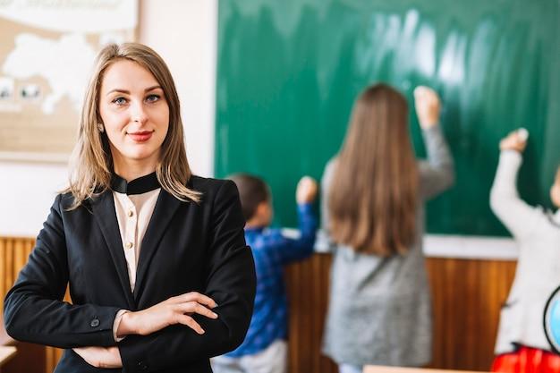 Vrouwelijke schoolleraar op de achtergrond van schoolbord en studenten