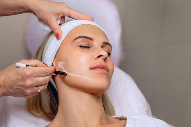 Vrouwelijke schoonheidsspecialist die een pijl op het gezicht van een vrouw trekt met een witte stift om zich voor te bereiden op de procedure.