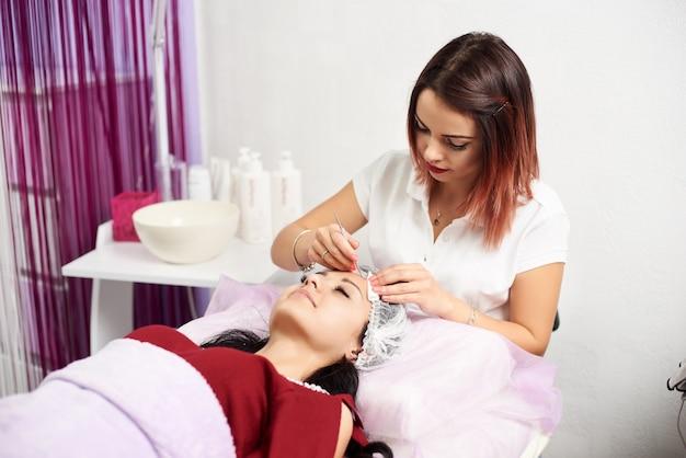 Vrouwelijke schoonheidsspecialist die gezichtsbehandeling geeft