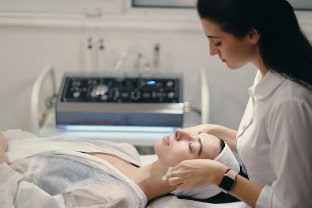 Vrouwelijke schoonheidsspecialist die gezichtsbehandeling tot een mooie woma maakt