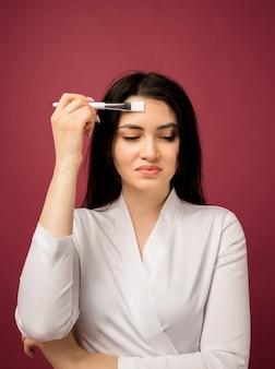 Vrouwelijke schoonheidsspecialist in een wit pak met een borstel op bordeaux