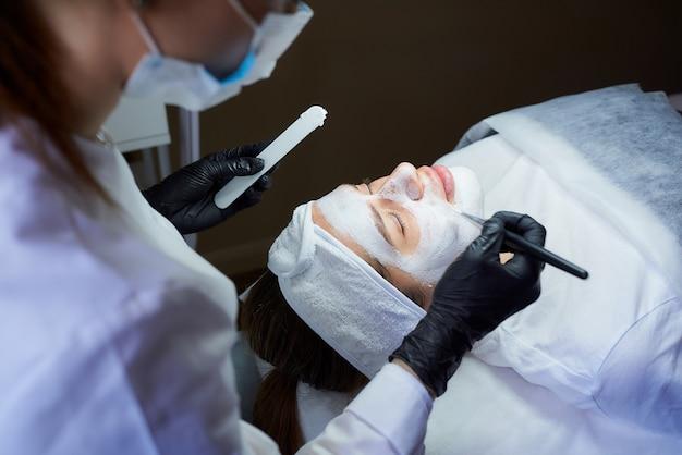 Vrouwelijke schoonheidsspecialist zijaanzicht die peeling gommage op het gezicht van het meisje toepast