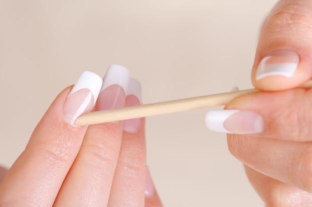 Vrouwelijke schoonmakende nagelriem op handen met een kosmetische stok