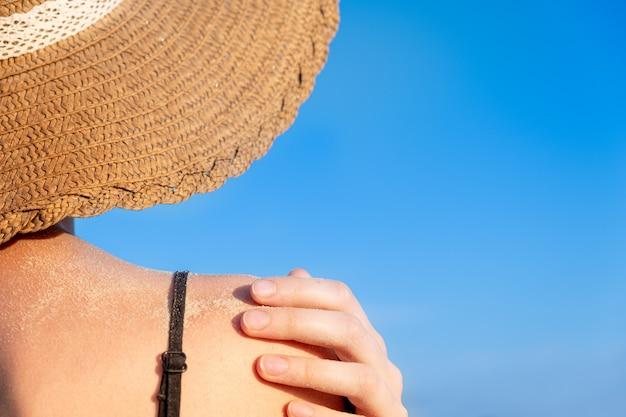 Vrouwelijke schouder bedekt met zand op heldere blauwe achtergrond.