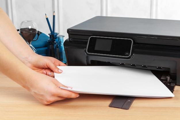 Vrouwelijke secretaresse die fotokopieën op xeroxmachine maakt in bureau